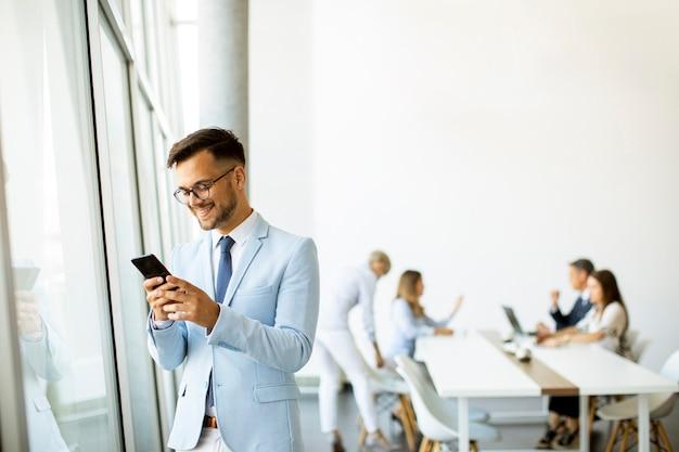Przystojny Młody Biznesmen Z Telefonem Komórkowym W Biurze Premium Zdjęcia