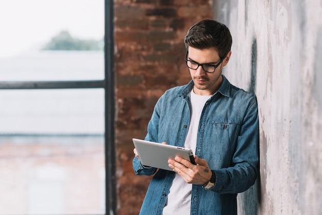 Przystojny młody człowiek jest ubranym eyeglasses używać cyfrową pastylkę Darmowe Zdjęcia