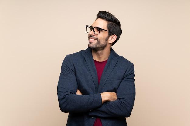 Przystojny Młody Człowiek Nad Odosobnioną ścianą Przyglądającą Up Podczas Gdy Ono Uśmiecha Się Premium Zdjęcia