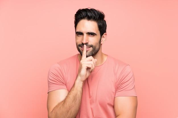 Przystojny młody człowiek nad odosobnionym różowym tłem robi cisza gestowi Premium Zdjęcia