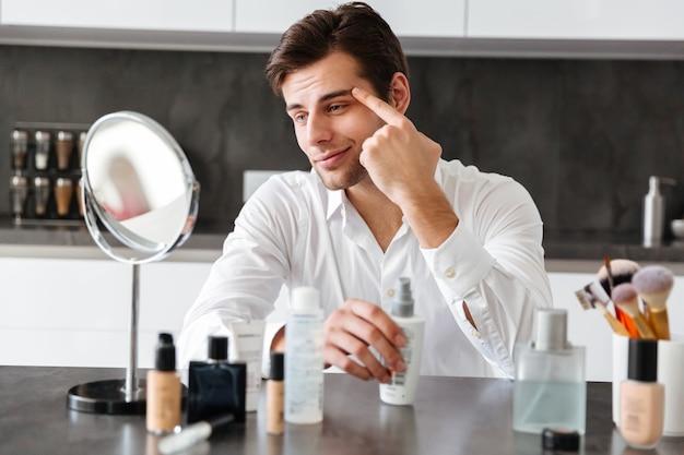 Przystojny Młody Człowiek Stosując Produkty Do Makijażu I Urody Darmowe Zdjęcia
