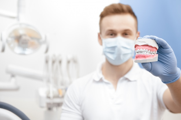 Przystojny Młody Męski Dentysta Demonstruje Zęby Foremkę Premium Zdjęcia