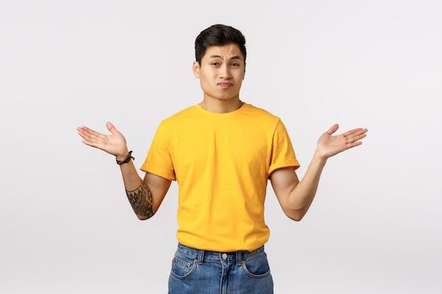 Przystojny Młody Mężczyzna Azji W żółty T-shirt Z Rozłożonymi Rękami Premium Zdjęcia