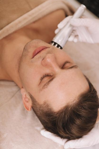 Przystojny Młody Mężczyzna Otrzymujących Zabiegi Pielęgnacyjne W Salonie Kosmetycznym Premium Zdjęcia