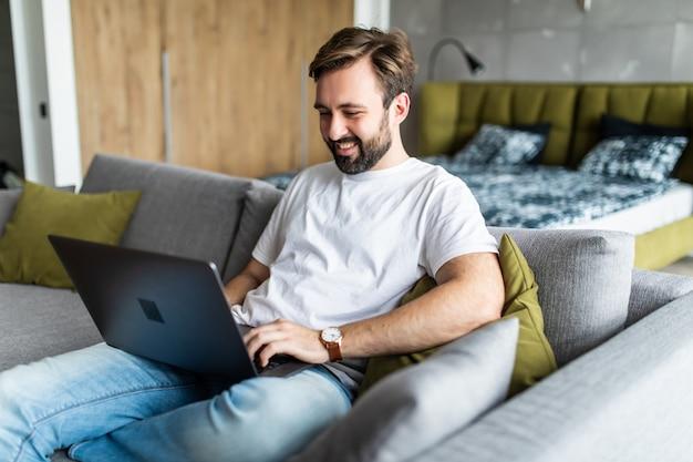 Przystojny Młody Mężczyzna Pracuje Na Swoim Laptopie, Relaksując Się Na Kanapie W Domu Premium Zdjęcia