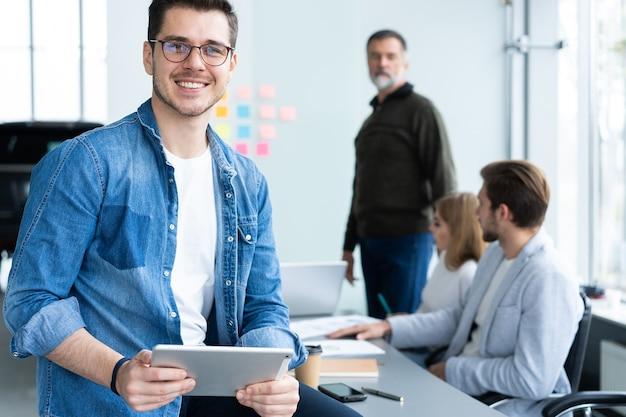 Przystojny Młody Mężczyzna Trzyma Cyfrowy Tablet I Uśmiecha Się W Biurze Premium Zdjęcia