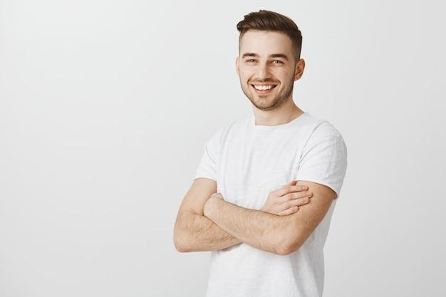 Przystojny Młody Mężczyzna W Białej Koszulce, Skrzyżowane Ramiona W Klatce Piersiowej I Uśmiechnięty Zadowolony Darmowe Zdjęcia