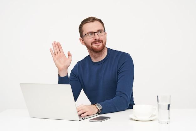 Przystojny Młody Nieogolony Jasnowłosy Mężczyzna Ubrany W Niebieski Sweter Podnoszący Dłoń W Geście Powitania, Patrząc Na Bok, Pracujący Z Laptopem Na Białym Tle Darmowe Zdjęcia