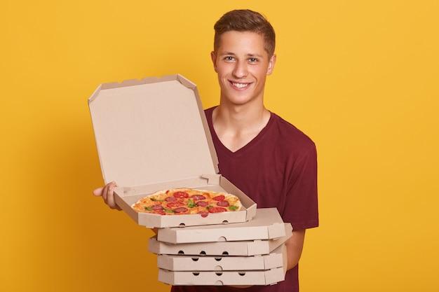 Przystojny Młody Pracownik Dostawy Posiadający Stos Pudełek Po Pizzy, Ubrany Na Co Dzień T Shirt, Patrząc Na Kamery I Uśmiechnięty, Pokazując Otwarte Pudełko Ze Smacznym Pepperoni, Pozowanie Na żółtym Studio Darmowe Zdjęcia
