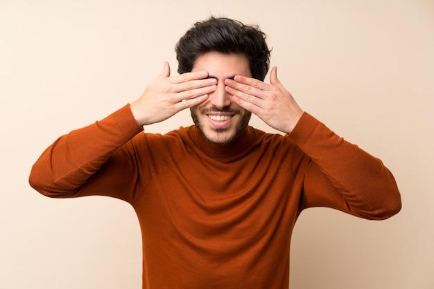 Przystojny na pojedyncze ściany obejmujące oczy rękami Premium Zdjęcia