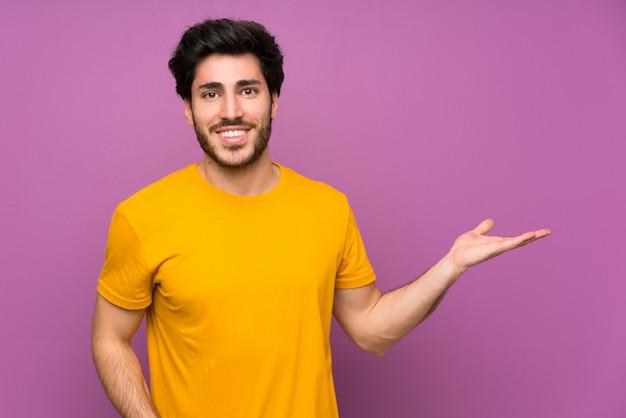 Przystojny Nad Odosobnioną Purpury ściany Mienia Copyspace Wyimaginowanym Na Dłoni, Aby Wstawić Reklamę Premium Zdjęcia