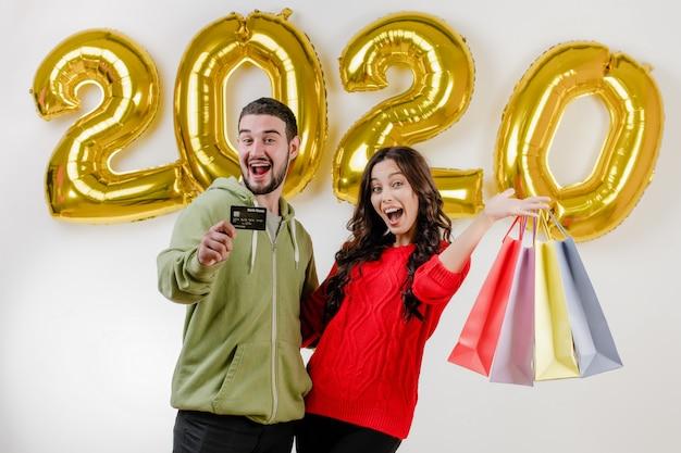 Przystojny para mężczyzna i kobieta trzyma karty kredytowej i kolorowe torby na zakupy przed 2020 balonów Premium Zdjęcia