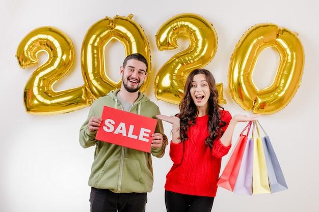 Przystojny para mężczyzna i kobieta trzyma sprzedaż znak i kolorowe torby na zakupy przed 2020 balonów Premium Zdjęcia