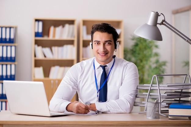 Przystojny pracownik obsługi klienta z zestawem słuchawkowym Premium Zdjęcia