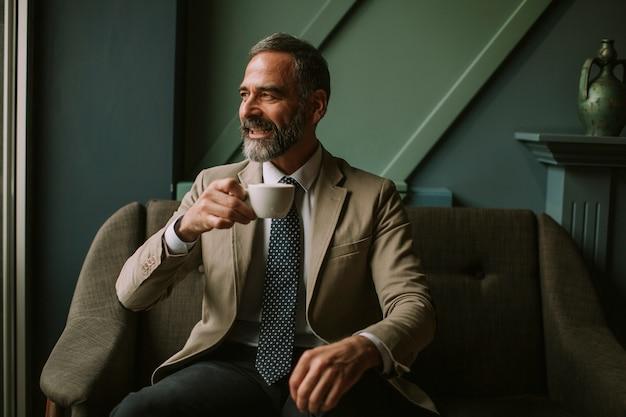 Przystojny starszy biznesmen pije kawę w lobby Premium Zdjęcia