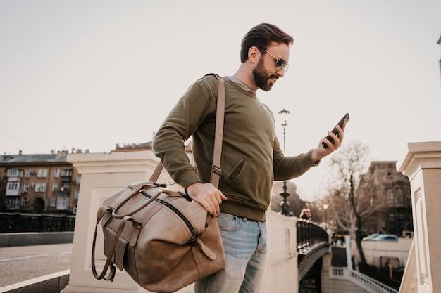 Przystojny Stylowy Hipster Mężczyzna Spacerujący Ulicą Miasta Ze Skórzaną Torbą Za Pomocą Aplikacji Do Nawigacji W Telefonie, Podróżujący W Bluzie I Okularach Przeciwsłonecznych, Trend W Stylu Miejskim Darmowe Zdjęcia