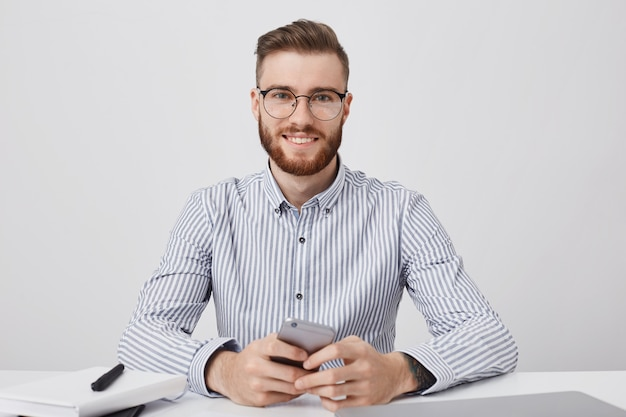 Przystojny Stylowy Mężczyzna Ubrany Formalnie, Siedzi Przy Biurku, Używa Smartfona Do Czytania Wiadomości Online Darmowe Zdjęcia