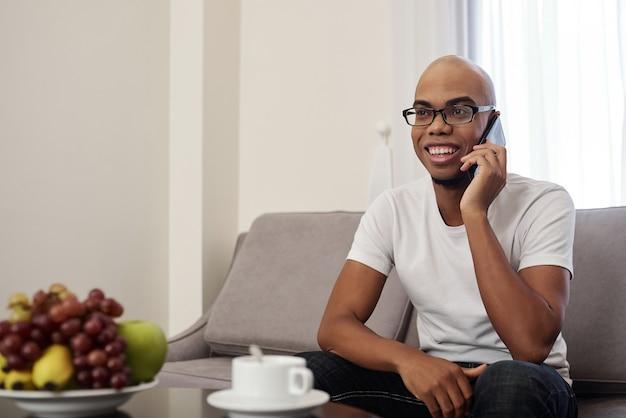 Przystojny Szczęśliwy Młody Murzyn Pije Kawę W Domu I Rozmawia Przez Telefon Z Przyjacielem Lub Krewnym Premium Zdjęcia