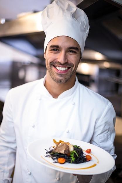 Przystojny Szef Kuchni Przedstawia Posiłek Premium Zdjęcia