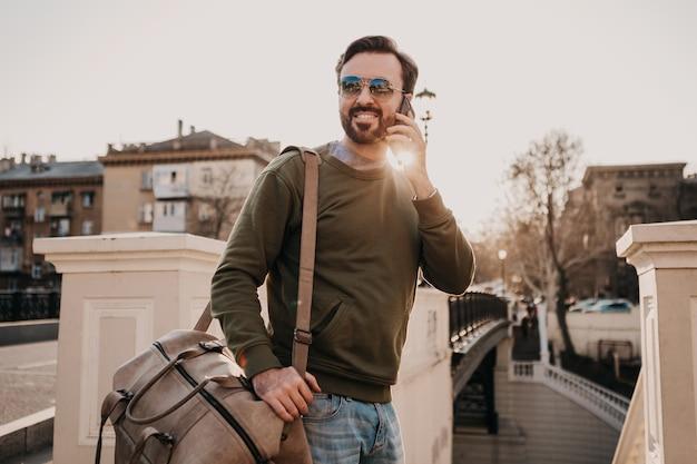 Przystojny Uśmiechnięty Stylowy Hipster Mężczyzna Spacerujący Ulicą Miasta Ze Skórą Rozmawiający Przez Telefon Na Torbie Podróżnej W Bluzie Dresowej I Okularach Przeciwsłonecznych, Trend W Stylu Miejskim, Słoneczny Dzień, Podróżowanie Darmowe Zdjęcia