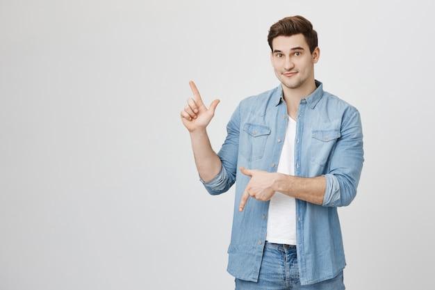 Przystojny Wesoły Student Płci Męskiej Wskazując W Górę Iw Dół Na Banery Darmowe Zdjęcia
