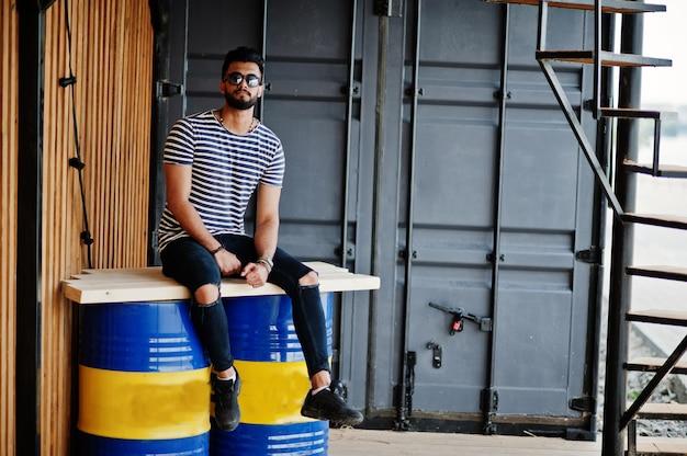 Przystojny Wysoki Model Arabski Broda Mężczyzna W Pasiastej Koszuli Postawił Na Zewnątrz. Modny Facet W Okularach Arabskich. Premium Zdjęcia