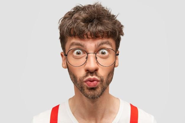 Przystojny, Zdziwiony Mężczyzna O Oszołomionej Minie, Zaokrągla Usta I Szeroko Otwiera Oczy, Nie Może Uwierzyć W Najnowsze Wiadomości Darmowe Zdjęcia