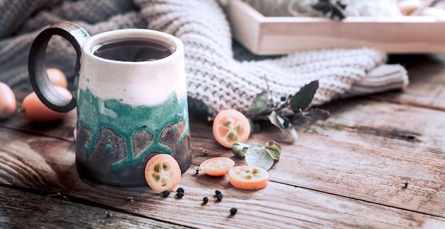 Przytulna Filiżanka Herbaty Z Swetrem Na Drewnianym Stole Premium Zdjęcia