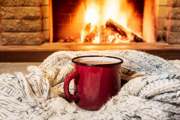 Przytulna scena przy kominku z czerwonym emaliowanym kubkiem z gorącą herbatą i przytulnym ciepłym szalikiem. Premium Zdjęcia
