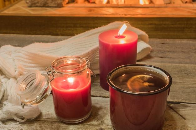 Przytulna scena przy kominku z kubkiem gorącej herbaty, ciepłym szalikiem i świecami. Premium Zdjęcia