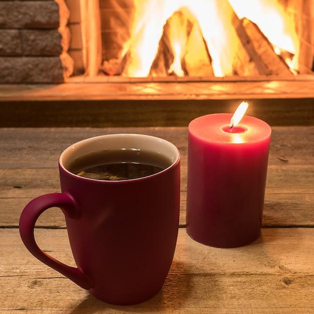 Przytulna scena przy kominku z kubkiem gorącej herbaty i świecy. Premium Zdjęcia