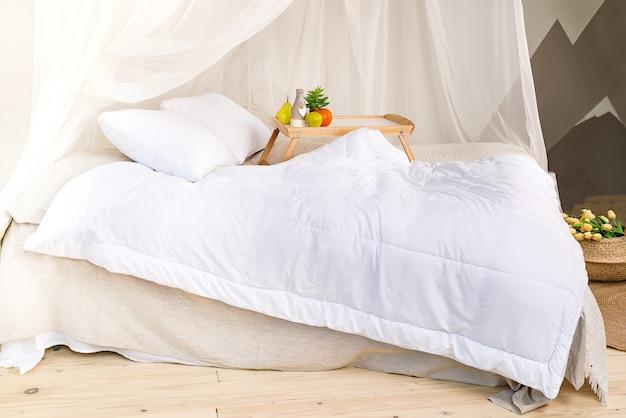 Przytulna sypialnia w pastelowych kolorach z drewnianą podłogą, dużym łóżkiem z baldachimem, tacą z br Premium Zdjęcia