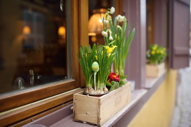 Przytulne okno drewnianego domu ozdobione kwiatami i drewnianymi ozdobami na wielkanoc. Premium Zdjęcia