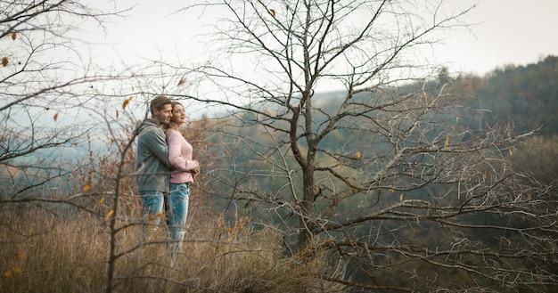 Przytulona Para Zakochanych Stoi Na Zboczu Wzgórza, Patrząc W Dół, Młody Mężczyzna I Kobieta Podziwiają Jesienny Las Rosnący Na Zboczach Poniżej Premium Zdjęcia