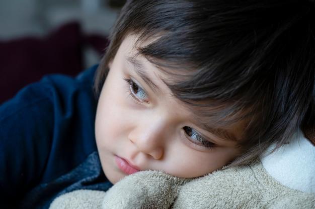 Przytulona Twarz Smutnego Dzieciaka Leżącego Z Głową Na Misiu, Szczera, Krótka Samotna Głowa Dziecka Na Swojej Zabawce Spoglądająca Głęboko W Zamyśleniu, Snape Zastrzelił Małego Chłopca Siedzącego Samotnie. Premium Zdjęcia