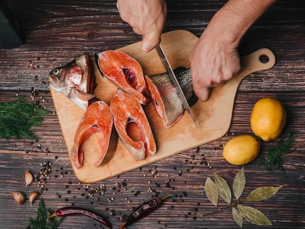 Pstrąg na desce krojony przez kucharza nożem Premium Zdjęcia