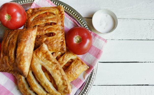 Ptysiowy Ciasto Z Pomidorem Na Białym Drewnianym Stole Z Kopii Przestrzenią Premium Zdjęcia