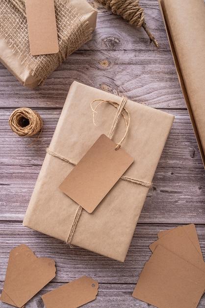Pudełka Na Prezenty Owinięte W Papier Rzemiosła Z Metkami I Etykietami Na Drewnianym Płaskim Widoku Z Góry Leżały Premium Zdjęcia