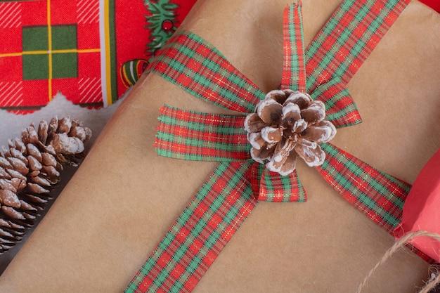 Pudełka Na Prezenty świąteczne Ozdobione Szyszkami Na Białej Powierzchni Darmowe Zdjęcia