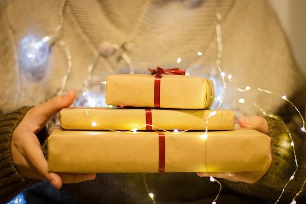 Pudełka Z Czerwoną Wstążką W Rękach. Ręce Trzymaj Prezenty W Ręcznie Robionym Papierze Z świecącą Girlandą Premium Zdjęcia