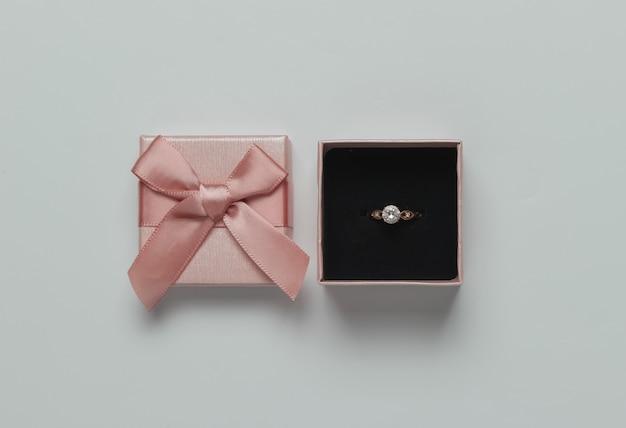 Pudełko I Złoty Pierścionek Z Brylantem Na Pastelowym Różowym Tle. Koncepcja ślubu. Biżuteria. Widok Z Góry. Leżał Na Płasko Premium Zdjęcia