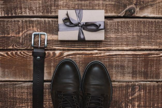 Pudełko Na Dzień Ojca Z Męskim Paskiem Na Akcesoria I Skórzanymi Butami Na Drewnianym Stole. Leżał Płasko. Premium Zdjęcia