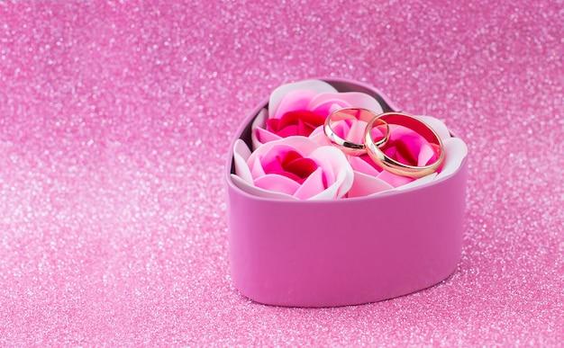 Pudełko Niespodzianka Prezent Różowe Serce Ze Złotymi Obrączkami ślubnymi Z Różami Na Błyszczącym Tle Z Bokeh Na Walentynki Premium Zdjęcia