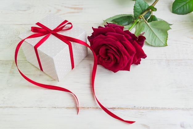 Pudełko prezentowe beżowe kropki z czerwoną wstążką łuku i piękne czerwone róże na drewniane tła. kartkę z życzeniami na wakacje. Premium Zdjęcia