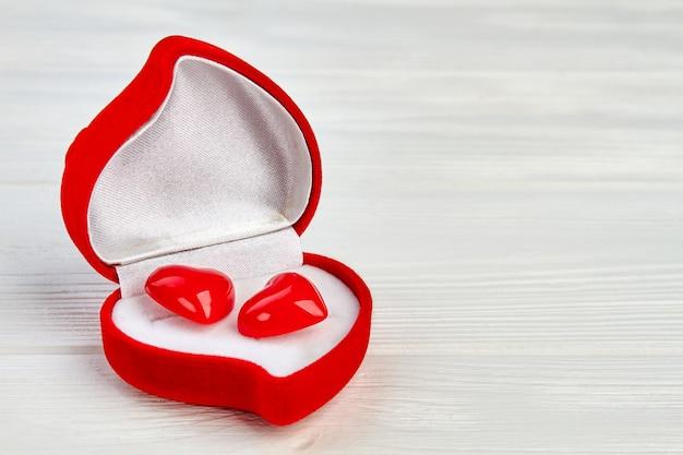 Pudełko W Kształcie Serca Z Czerwonymi Kolczykami. Pudełko Na Prezent Walentynki Z Dwoma Czerwonymi Akcesoriami W Kształcie Serca I Miejscem Na Kopię. Premium Zdjęcia