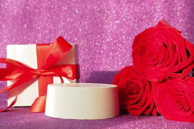 Pudełko Z Czerwoną Kokardą I Podium Na Fioletowym Błyszczącym Tle Premium Zdjęcia