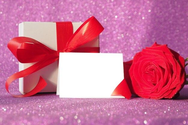 Pudełko Z Czerwoną Kokardką I Czerwoną Różą Na Fioletowym Błyszczącym Tle Premium Zdjęcia