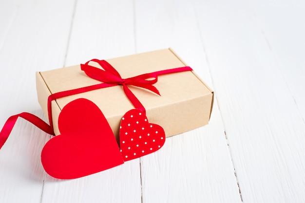 Pudełko Z Czerwoną Wstążką, Dwa Czerwone Serca Na Białym Tle Drewnianych. Walentynki Tło Z Kopii Przestrzenią Premium Zdjęcia
