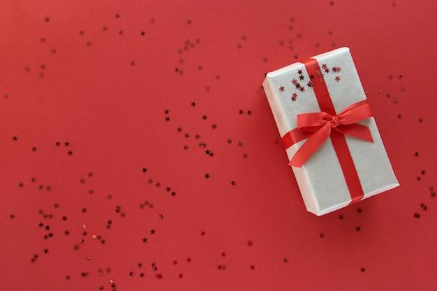 Pudełko Z Czerwoną Wstążką I Dekoracjami Konfetti Na Pastelowym Papierze Kolorowe Tło. Leżał Na Płasko, Widok Z Góry, Miejsce Na Kopię Premium Zdjęcia