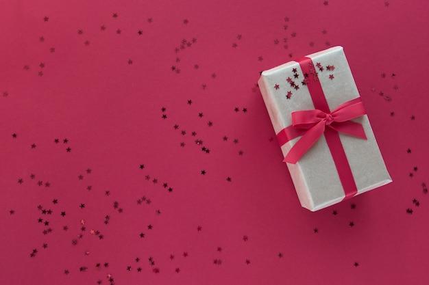 Pudełko Z Czerwoną Wstążką I Dekoracjami Konfetti Na Pastelowym Papierze Kolorowe Tło Premium Zdjęcia